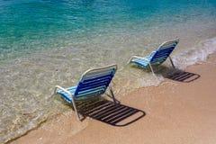 Cadeiras de praia azuis no mar na praia em Roatan fotografia de stock royalty free