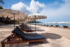 Cadeiras de praia com guarda-chuva e a praia bonita Imagem de Stock