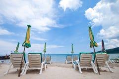Cadeiras de praia com guarda-chuva e a praia bonita Fotos de Stock