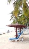 Cadeiras de praia de madeira brancas com coxim azul e máscaras de madeira em t Fotos de Stock Royalty Free