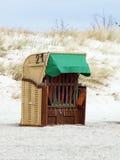 Cadeiras de praia de vime telhadas na praia imagem de stock