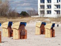 Cadeiras de praia de vime telhadas na praia fotografia de stock
