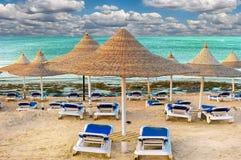 Cadeiras de praia e com o guarda-chuva na praia Imagens de Stock