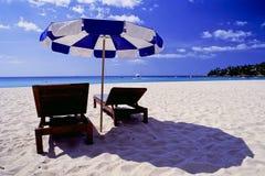 Cadeiras de praia e para-sol Fotos de Stock