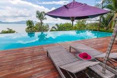 Cadeiras de praia pela piscina com opinião bonita do mar foto de stock
