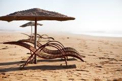 Cadeiras de praia vazias em uma praia imagem de stock