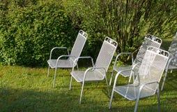 Cadeiras de prata metálicas no parque na grama Imagem de Stock Royalty Free