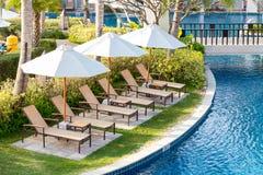 Cadeiras de relaxamento ao lado da piscina no jardim residencial Fotos de Stock Royalty Free