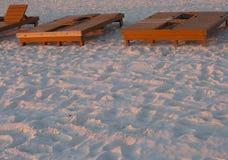 Cadeiras de sala de estar alugados da praia no por do sol fotos de stock