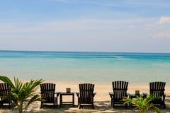 Cadeiras de sala de estar com guarda-chuva de sol em uma praia Sun das horas de verão no céu e a areia do abrandamento da praia a foto de stock