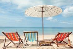 Cadeiras de sala de estar da praia sob o guarda-chuva na praia Imagens de Stock