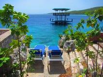 Cadeiras de sala de estar que negligenciam a plataforma do mar das caraíbas e da nadada Foto de Stock Royalty Free