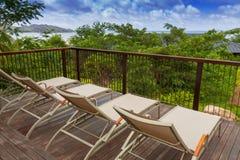 Cadeiras do banho de sol no decking de madeira Foto de Stock Royalty Free