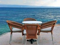 Cadeiras do café e tabela de madeira na frente do mar Imagens de Stock Royalty Free