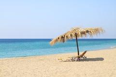 Cadeiras do guarda-chuva e de sala de estar na praia idílico imagem de stock royalty free