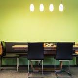 Cadeiras do modilhão na tabela da madeira com lâmpadas Imagem de Stock