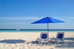 Cadeiras e guarda-chuva de praia pelo mar Foto de Stock