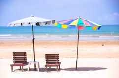 Cadeiras e guarda-chuvas de praia na praia da areia Imagens de Stock