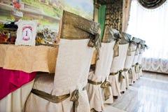 Cadeiras e quadro com número um na tabela do convidado no casamento com referência a Imagens de Stock Royalty Free