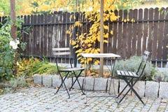 Cadeiras e tabela em um jardim do outono fotografia de stock royalty free