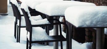 Cadeiras e tabelas cobertas fora na neve Foto de Stock