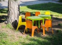 Cadeiras e tabelas plásticas das crianças na grama Fotos de Stock