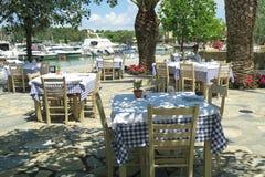 Cadeiras e tabelas vazias gregas do taverna por um porto em Grécia Fotos de Stock