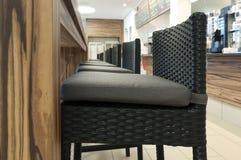 Cadeiras elevadas alinhadas do rattan na frente da tabela de madeira Fotografia de Stock