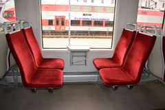 Cadeiras em um trem elétrico com estofamento vermelho do velor O interior do carro de trem fotografia de stock
