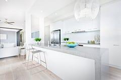 Cadeiras luxuosas da cozinha e luzes de suspensão com paredes brancas imagem de stock