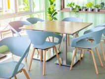 Cadeiras modernas e tabela de madeira no café imagem de stock