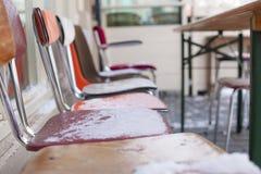 cadeiras Multi-coloridas na neve Inverno na cidade Um café da rua em Europa Curso e turismo Fotografia de Stock
