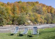 Cadeiras para descansar no banco do rio fotos de stock
