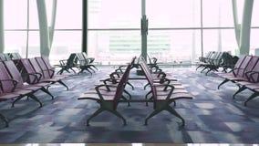 Cadeiras para o avião de espera na sala de estar da partida no aeroporto no fundo da janela Área e janela de espera no aeroporto vídeos de arquivo
