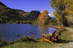 Cadeiras pelo lago Imagem de Stock