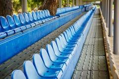 Cadeiras plásticas vazias nos suportes do estádio Fotografia de Stock