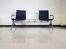 Cadeiras pretas na sala de espera vazia ordinária Fotos de Stock Royalty Free