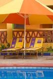 Cadeiras sob um guarda-chuva do Poolside Foto de Stock Royalty Free