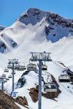 Cadeiras vagas do elevador do cabo aéreo de uma estância de esqui vazia no dia de inverno ensolarado em um fundo nevado do vertic Fotografia de Stock Royalty Free