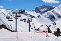 Cadeiras vagas do elevador do cabo aéreo de uma estância de esqui vazia no dia de inverno ensolarado em um fundo nevado do pico d Imagem de Stock