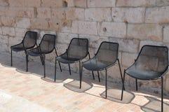 Cadeiras vazias na fileira sob a parede de pedra fotos de stock royalty free