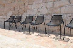 Cadeiras vazias na fileira sob a parede de pedra fotos de stock