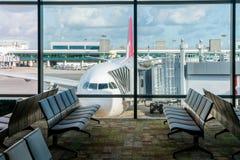 Cadeiras vazias no salão da partida no aeroporto com estacionamento do avião Curso e transporte em conceitos do aeroporto imagens de stock royalty free