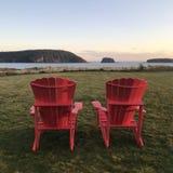 Cadeiras vermelhas do adirondack que negligenciam cinco ilhas Imagens de Stock Royalty Free