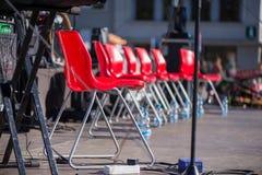 Cadeiras vermelhas em seguido na fase Imagem de Stock