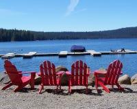 Cadeiras vermelhas quatro de Adirondack pelo lago Imagem de Stock