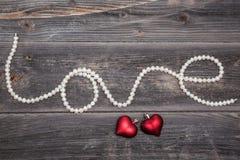 Cadena de amor de las perlas y de corazones rojos fotografía de archivo libre de regalías
