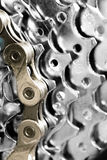 Cadena de la bicicleta del oro en los engranajes de plata Foto de archivo libre de regalías