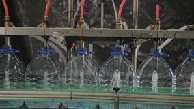 Cadena de producción del agua potable y bebidas carbónicas, el proceso de llenar las botellas de agua, transportador metrajes