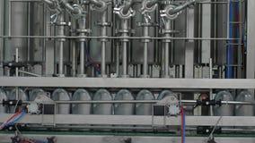 Cadena de producción de la fábrica, aceite sintético líquido de colada del motor del equipo adentro a las botellas plásticas gris almacen de video